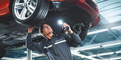 BMW mechanic performing brake inspection to a BMW vehicle