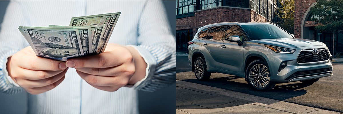 Person holding money and a 2021 toyota highlander parked on the side of a city road during the day with a brick building in the background
